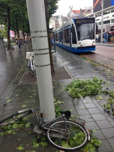A street in Amsterdam with toppled bikes, tree branches, and a tram unable to push through the horrendous torrents.